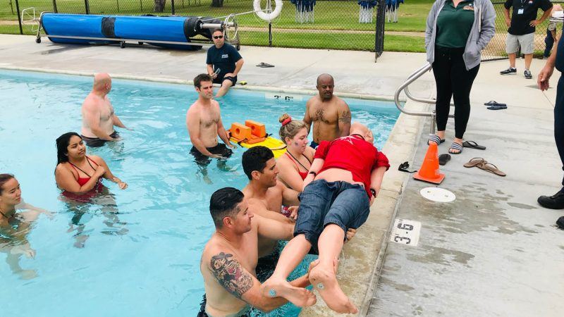 People lifting CPR dummy out of pool.