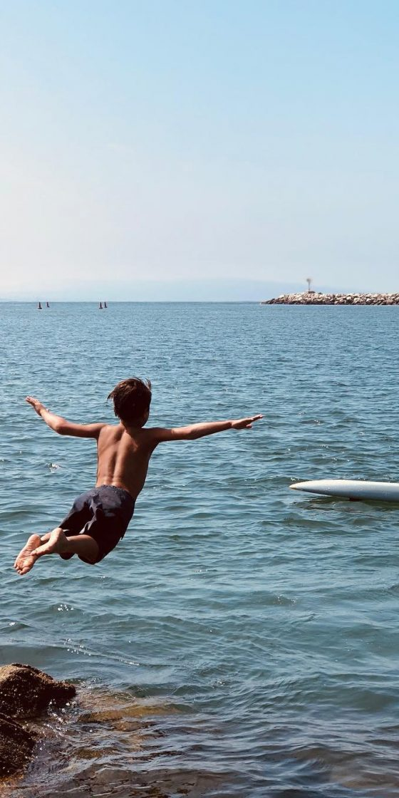 Junior Lifeguard diving off a cliff into the water to swim.