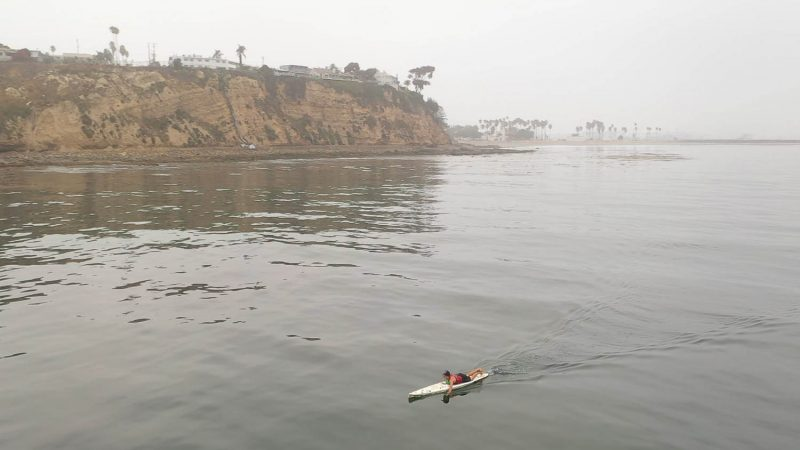 Zoomed out image of a lifeguard paddling.