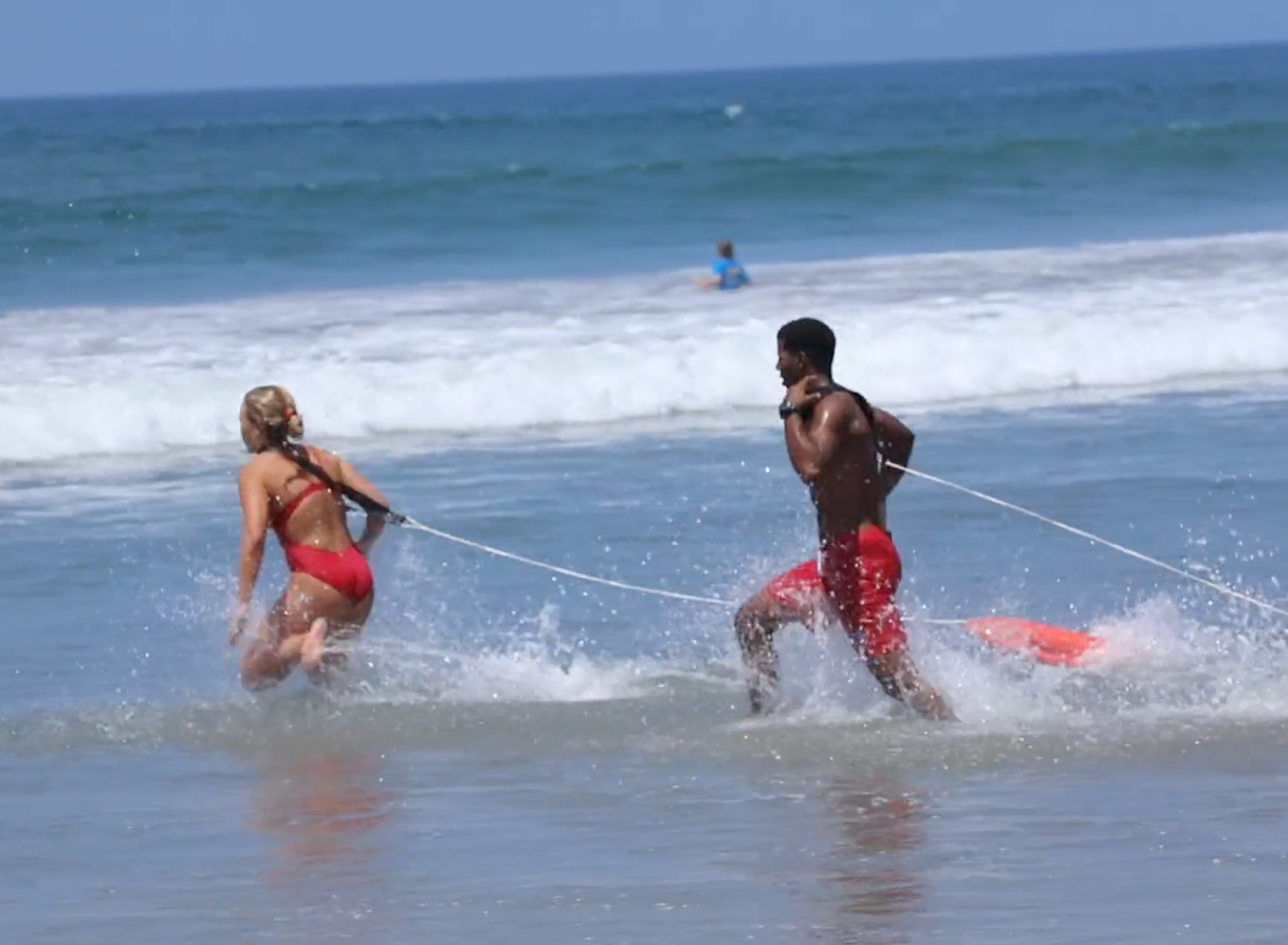 two lifeguards going into the water.