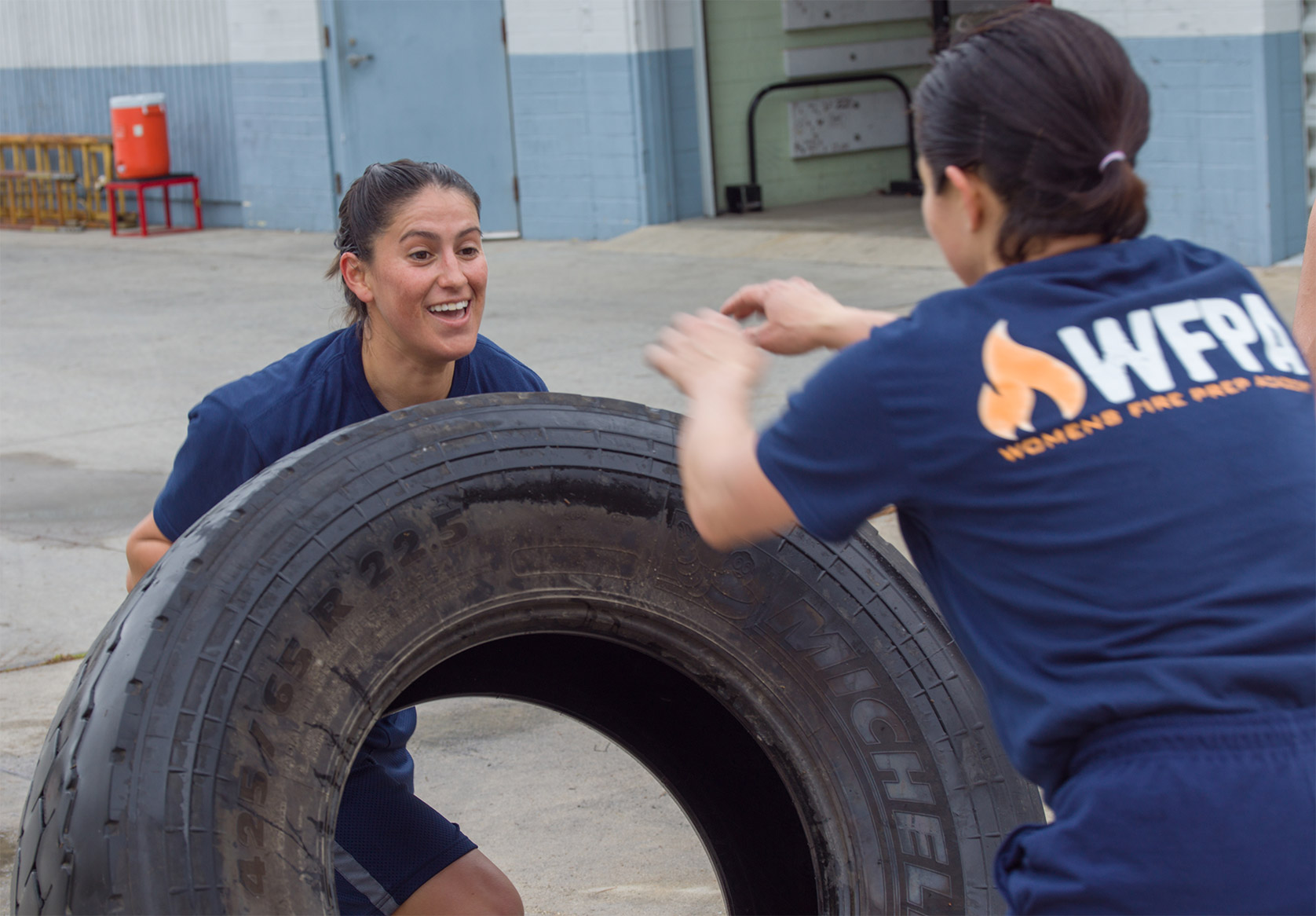 Womens Fire Prep Academy lifting a tire.