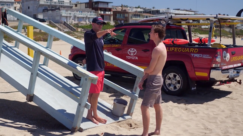 Lifeguard talking to person.
